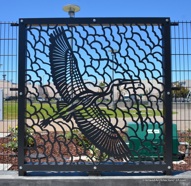 The plaque that accompanies this panel reads: The great blue heron depicted here life-size, has a wingspan of approximately 6 1/2 feet.  Mission Creek that runs beneath this site historically provided a habitat and hunting ground for the great blue heron in its search for frogs, fish, gophers and other animals.  Here the bird carries a leafless branch, the building materials for its nest.